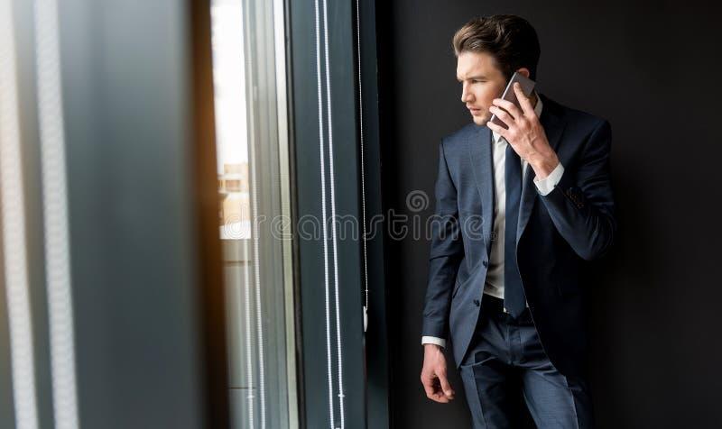 Ο καταθλιπτικός σκυθρωπός επιχειρηματίας μιλά στο smartphone στοκ εικόνα με δικαίωμα ελεύθερης χρήσης
