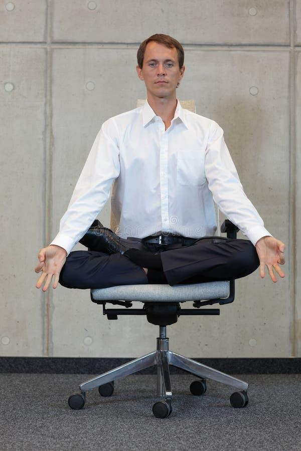 Ο καυκάσιος επιχειρηματίας Meditating στο λωτό θέτει στην καρέκλα γραφείων στοκ φωτογραφίες