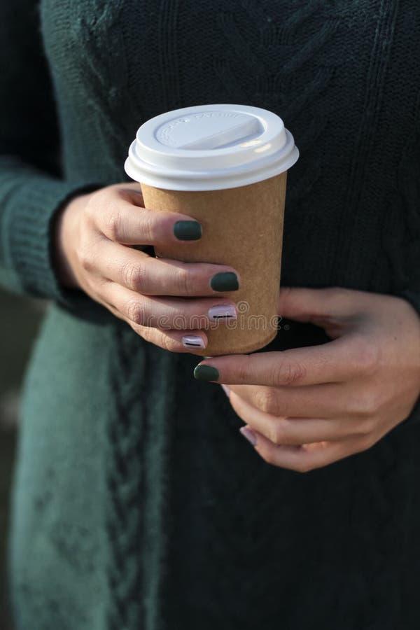 Ο καφές για να πάει της γυναίκας εκμετάλλευσης φλυτζανιών παραδίδει το πάρκο φθινοπώρου στοκ εικόνα