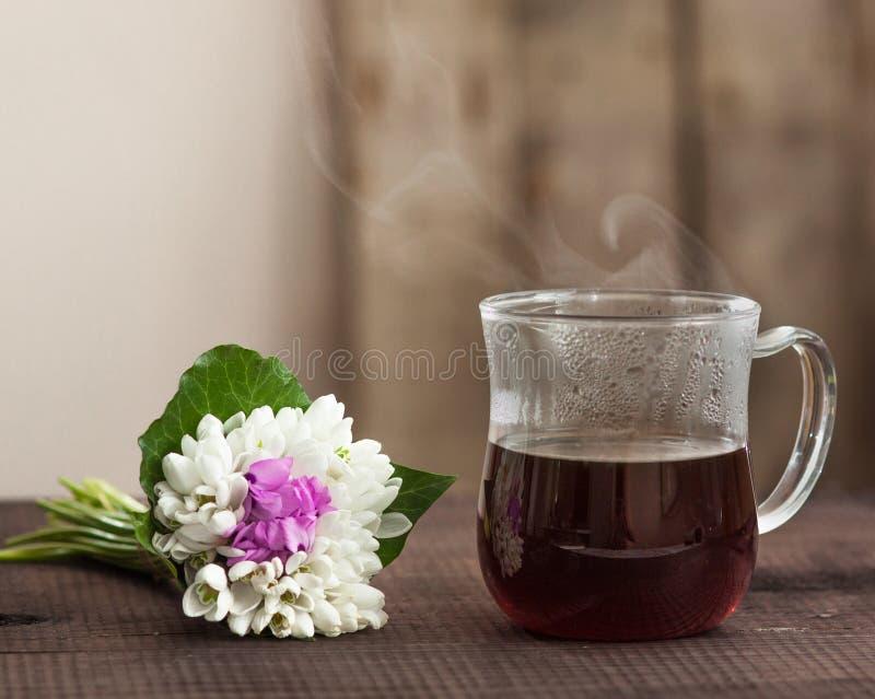 Ο καφές πρωινού στο φλυτζάνι γυαλιού με το φρέσκο ελατήριο ανθίζει bouqet στο ξύλινο υπόβαθρο στοκ εικόνες