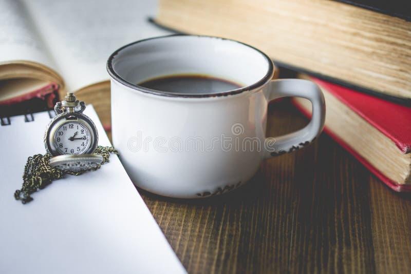Ο καφές στο παλαιό φλυτζάνι και η τσέπη προσέχουν σε ξύλινο με το βιβλίο σε VI στοκ εικόνα με δικαίωμα ελεύθερης χρήσης
