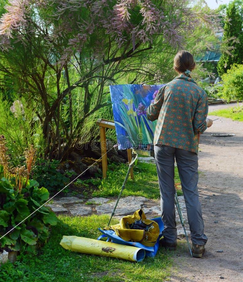 Ο καλλιτέχνης κοριτσιών σύρει τα λουλούδια από τη ζωή στοκ εικόνα