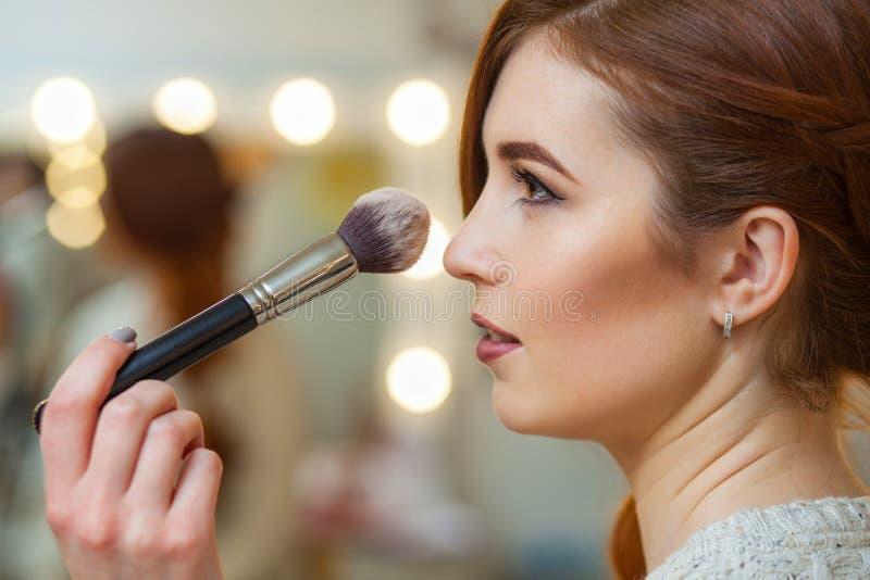 Ο καλλιτέχνης σύνθεσης βάζει τη σκόνη στο πρόσωπο ενός όμορφου, κοκκινομάλλους κοριτσιού στο σαλόνι ομορφιάς στοκ εικόνες