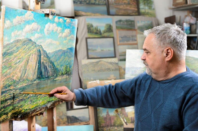 Ο καλλιτέχνης χρωματίζει τη ελαιογραφία με μια βούρτσα και μια παλέτα στοκ εικόνες με δικαίωμα ελεύθερης χρήσης