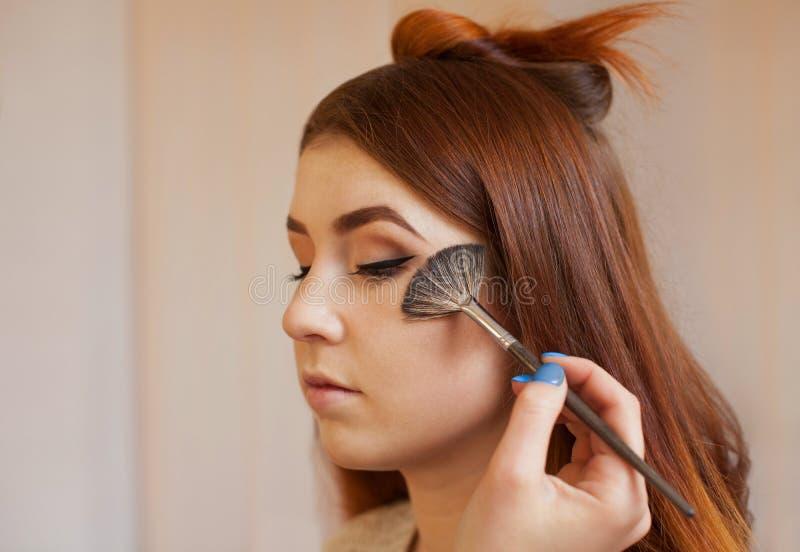 Ο καλλιτέχνης Makeup που εφαρμόζεται με μια βούρτσα κοκκινίζει στο πρόσωπο κοριτσιών ` s, ολοκληρώνει την καθημερινή σύνθεση σε έ στοκ φωτογραφίες με δικαίωμα ελεύθερης χρήσης