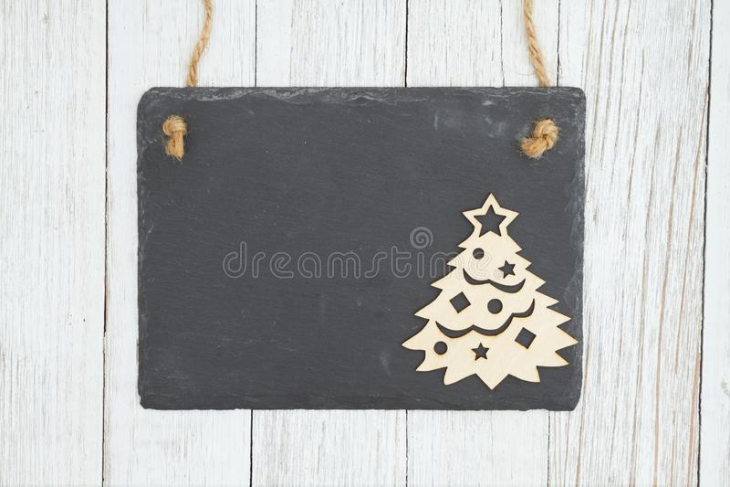 Ο κενός κρεμώντας πίνακας κιμωλίας με ένα χριστουγεννιάτικο δέντρο ξεπερασμένος ασπρίζει το κατασκευασμένο ξύλινο υπόβαθρο στοκ φωτογραφίες με δικαίωμα ελεύθερης χρήσης