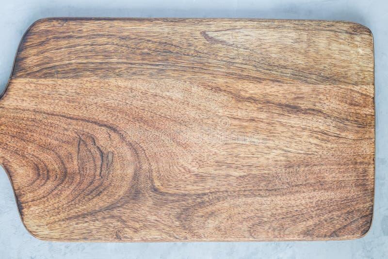 Ο κενός ξύλινος τέμνων πίνακας στο συγκεκριμένο υπόβαθρο, αντιγράφει τη διαστημική, τοπ άποψη, οριζόντια στοκ εικόνα