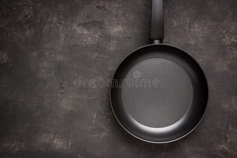 Ο κενός τηγανίζοντας παν Μαύρος στη σκοτεινή πέτρινη επιφάνεια στοκ εικόνες
