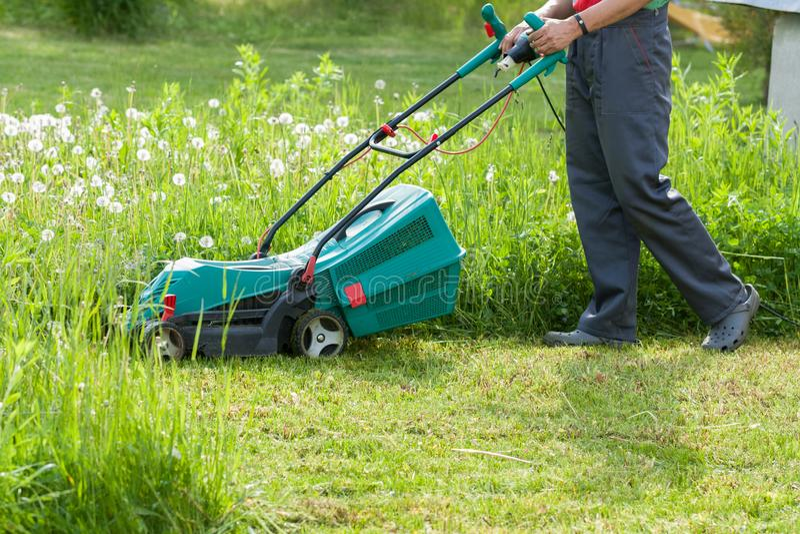 Ο κηπουρός κόβει τη χλόη με το θεριστή χορτοταπήτων στον κήπο στοκ φωτογραφία