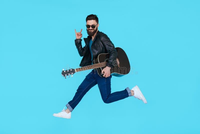 Ο κιθαρίστας ατόμων πηδά παρουσιάζοντας χειρονομία βράχου στοκ εικόνες