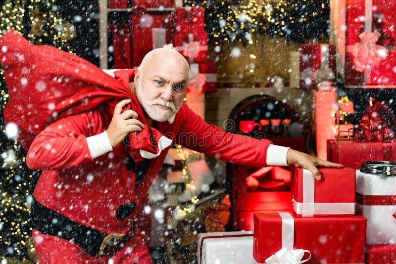 Ο κλέφτης έκλεψε τα δώρα των νέων χρόνων Χριστούγεννα Ο εγκληματικός Άγιος Βασίλης ποζάρει με μια τσάντα με χριστουγεννιάτικα δώρ στοκ εικόνες με δικαίωμα ελεύθερης χρήσης