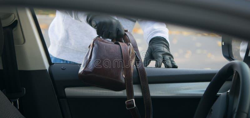 Ο κλέφτης παίρνει μια τσάντα των εγγράφων μέσω του ανοίγματος παραθύρων του αυτοκινήτου στοκ εικόνα
