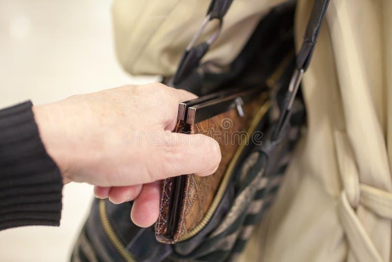 Ο κλέφτης πορτοφολάδων είναι stealing πορτοφόλι από την τσάντα στοκ εικόνες με δικαίωμα ελεύθερης χρήσης