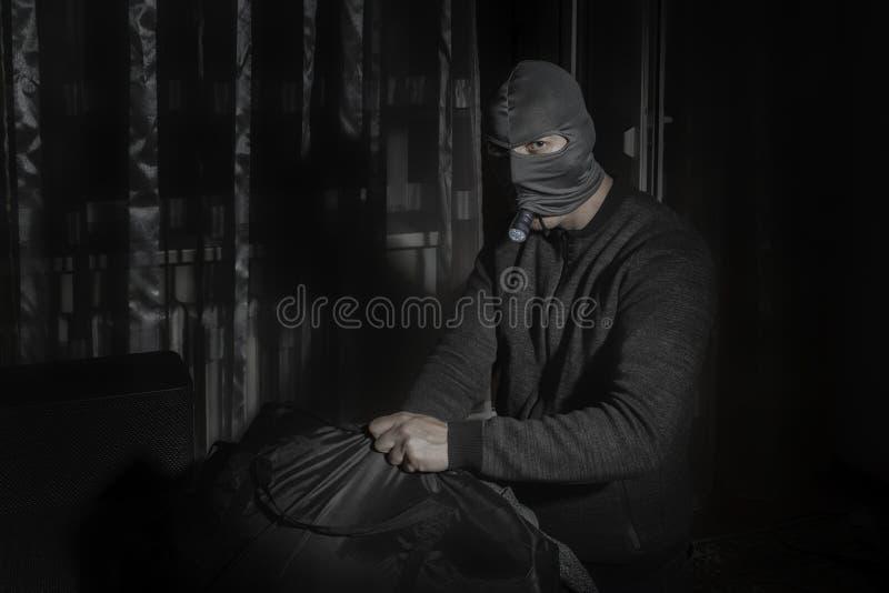 Ο κλέφτης σε μια μάσκα και με έναν φακό στο δωμάτιο βάζει το λάφυρο στην τσάντα στοκ φωτογραφία