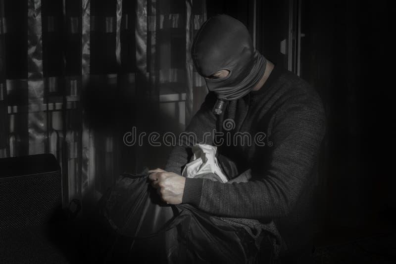 Ο κλέφτης σε μια μάσκα και με έναν φακό στο δωμάτιο βάζει το λάφυρο σε μια τσάντα στοκ εικόνες με δικαίωμα ελεύθερης χρήσης