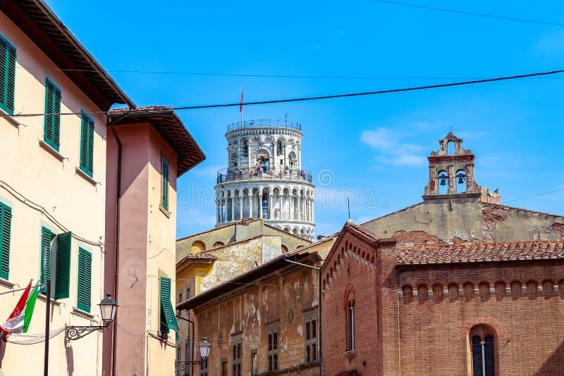 Ο κλίνοντας πύργος της Πίζας που βλέπει ανάμεσα στα χαρακτηριστικά τοπικά κτήρια στοκ εικόνα