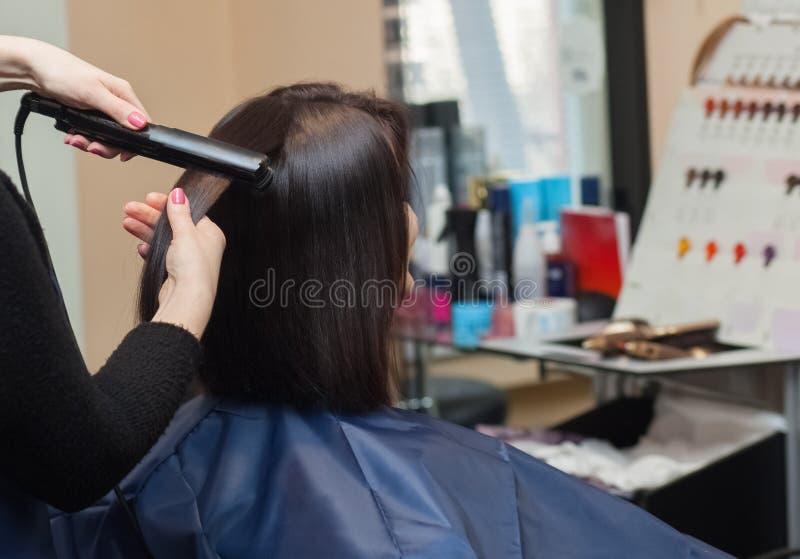 Ο κομμωτής κάνει ευθυγραμμίζει την τρίχα με το σίδηρο τρίχας σε ένα νέο κορίτσι στοκ φωτογραφία