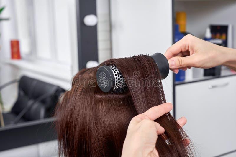 Ο κομμωτής κινηματογραφήσεων σε πρώτο πλάνο κάνει hairstyle για τη νέα γυναίκα στο σαλόνι ομορφιάς στοκ φωτογραφίες με δικαίωμα ελεύθερης χρήσης