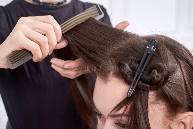 Ο κομμωτής κινηματογραφήσεων σε πρώτο πλάνο κάνει hairstyle για τη νέα γυναίκα στο σαλόνι ομορφιάς στοκ εικόνα με δικαίωμα ελεύθερης χρήσης