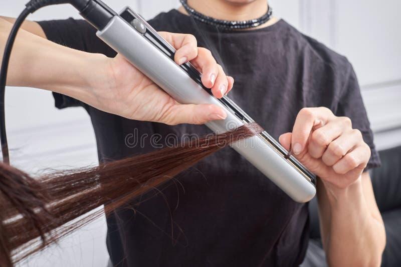 Ο κομμωτής κινηματογραφήσεων σε πρώτο πλάνο κάνει hairstyle για τη νέα γυναίκα στο σαλόνι ομορφιάς στοκ φωτογραφία με δικαίωμα ελεύθερης χρήσης