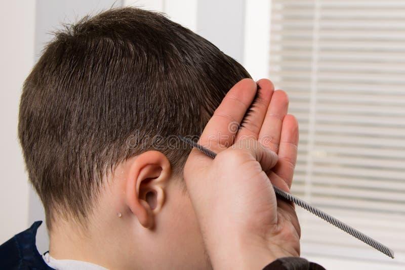 Ο κομμωτής κρατά μια χτένα στο χέρι του και κάνει ένα hairdo για το αγόρι στοκ φωτογραφία
