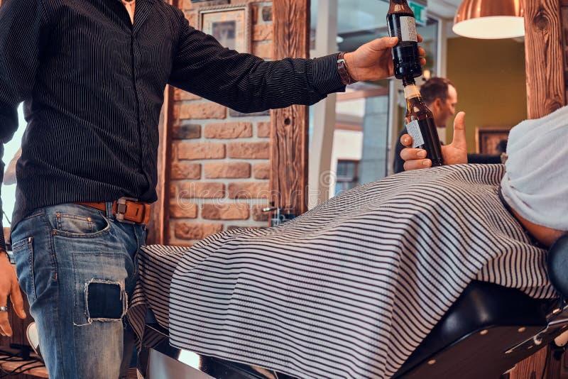 Ο κομμωτής Thendy στο σύγχρονο barbershop εργάζεται στο κούρεμα του πελάτη στοκ εικόνα