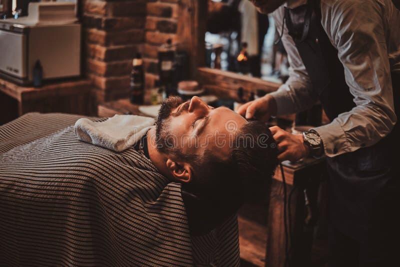 Ο κομμωτής Thendy στο σύγχρονο barbershop εργάζεται στο κούρεμα του πελάτη στοκ εικόνα με δικαίωμα ελεύθερης χρήσης