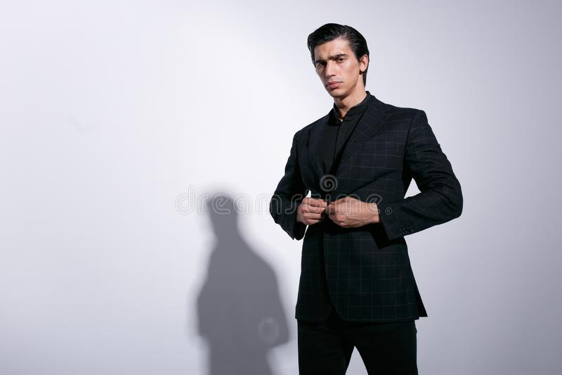 Ο κομψός νεαρός άνδρας στο πλήρες μαύρο κοστούμι, τακτοποίησε το σακάκι του, εξετάζοντας σοβαρός τη κάμερα, που απομονώθηκε σε έν στοκ φωτογραφίες