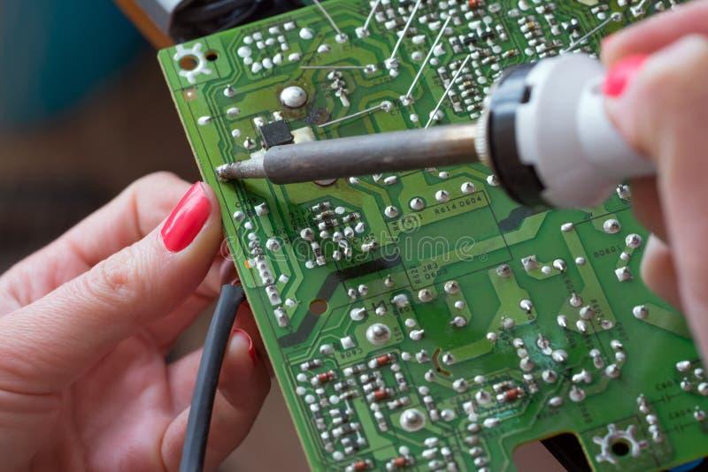 Ο κορίτσι-μηχανικός επισκευάζει μια παροχή ηλεκτρικού ρεύματος ώθησης μετατροπής Εγκατάσταση και συγκόλληση των ηλεκτρονικών συστ στοκ φωτογραφία με δικαίωμα ελεύθερης χρήσης