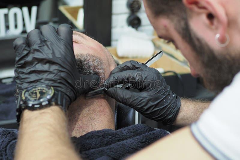 Ο κουρέας ξυρίζει τη γενειάδα ενός ηληκιωμένου με το γκρίζο αιχμηρό ξυράφι τρίχας στοκ φωτογραφία