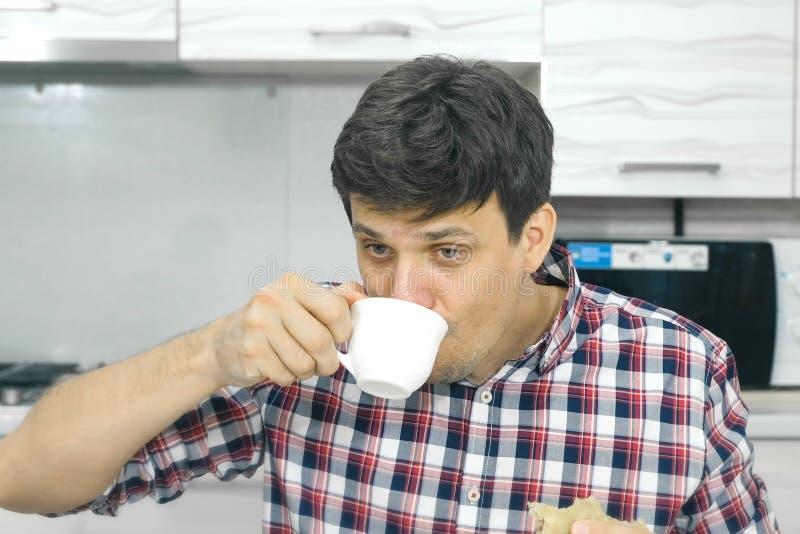 Ο κουρασμένος νεαρός άνδρας σε ένα πουκάμισο καρό τρώει ένα μεγάλο cheburek με μια όρεξη και τα ποτά στοκ φωτογραφία με δικαίωμα ελεύθερης χρήσης