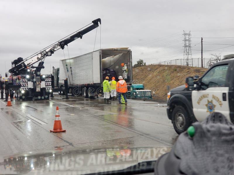 Ο Κρέιν δουλεύει δεξιά σε φορτηγό αφού ανατράπηκε στη βροχή στοκ εικόνες με δικαίωμα ελεύθερης χρήσης