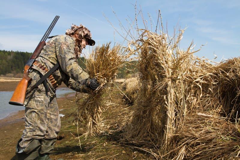 Ο κυνηγός παπιών χτίζει ένα κυνήγι τυφλό των καλάμων στοκ εικόνες