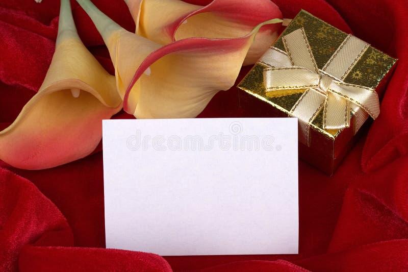 Ο κόκκινος και κίτρινος calla κρίνος ανθίζει το χρυσό κιβώτιο δώρων με την κίτρινη κορδέλλα στην κόκκινη κάρτα υποβάθρου υφάσματο στοκ εικόνες