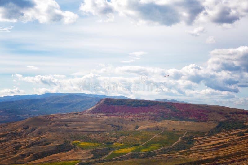 Ο κόκκινος καπνισμένος φθινόπωρο Μπους και όμορφη άποψη των βουνών Karadag στοκ εικόνα