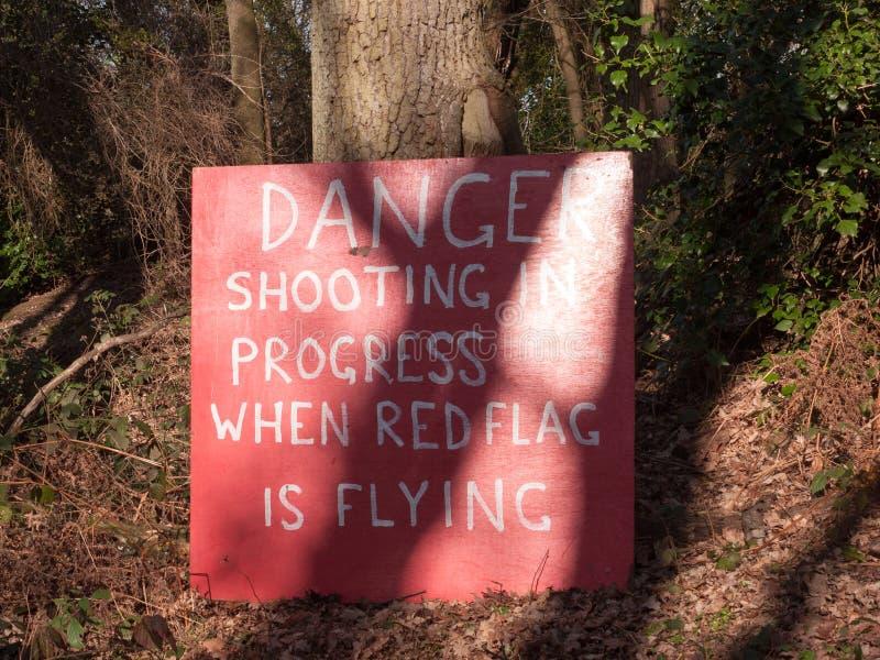 Ο κόκκινος πυροβολισμός κινδύνου κορμών δέντρων σημαδιών είναι υπό εξέλιξη όταν κόκκινη σημαία στοκ εικόνα με δικαίωμα ελεύθερης χρήσης