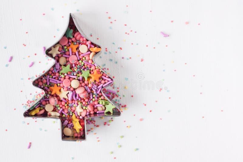 Ο κόπτης μπισκότων χριστουγεννιάτικων δέντρων με τη ζάχαρη ψεκάζει στοκ εικόνες