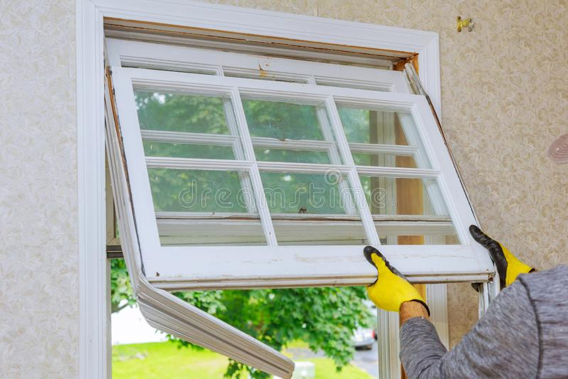 Ο κύριος αφαιρεί τις παλαιές εγχώριες επισκευές, παράθυρα αντικατάστασης στοκ φωτογραφία με δικαίωμα ελεύθερης χρήσης