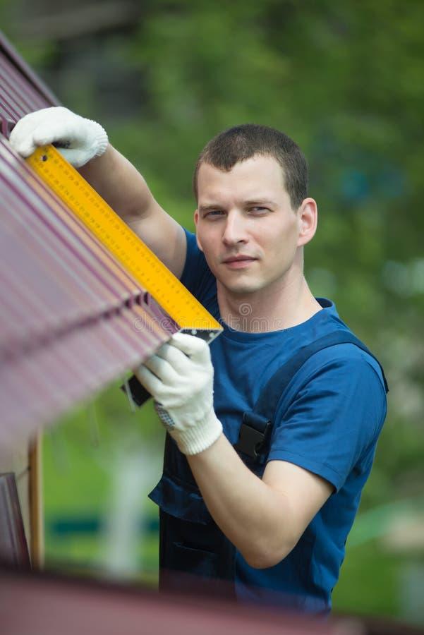 ο κύριος επισκευάζει τη στέγη ενός σπιτιού στοκ φωτογραφία με δικαίωμα ελεύθερης χρήσης