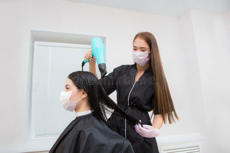Ο κύριος κομμωτής χτυπά τα μαλλιά του πελάτη με ένα στεγνωτήριο μαλλιών, με ανάκτηση κερατίνης ιδέα για τη φροντίδα των παιδιών στοκ εικόνες με δικαίωμα ελεύθερης χρήσης