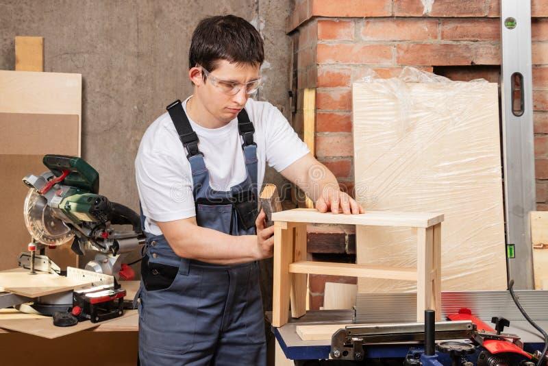 Ο κύριος ξυλουργός ξεφλουδίζει το σκαμνί στοκ φωτογραφία