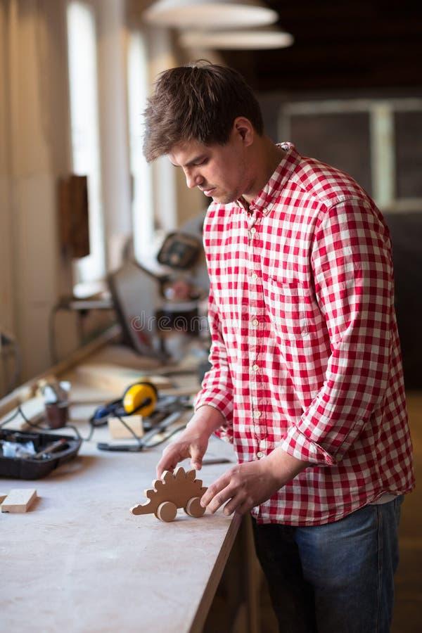 Ο κύριος ξυλουργός το ξύλινο παιχνίδι λεπτομερειών που γίνεται συνδέει με τα χέρια σας, στοκ εικόνες