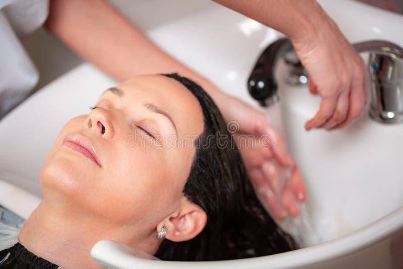 Ο κύριος πλένει το κεφάλι του πελάτη στο κατάστημα κουρέων, ο κομμωτής κάνει hairstyle για μια νέα γυναίκα στοκ εικόνα