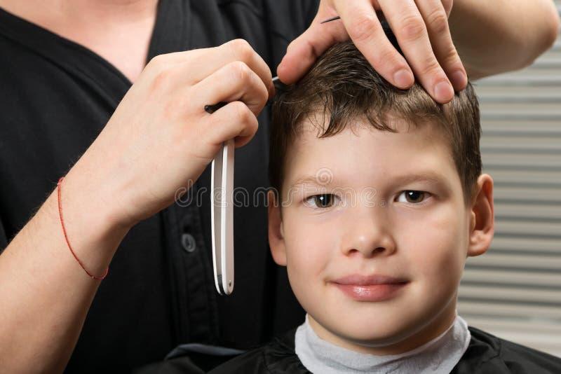 Ο κύριος στιλίστας, κάνει το αγόρι ένα ευθύ μέρος στην τρίχα του, μια επικίνδυνη λεπίδα στοκ εικόνες