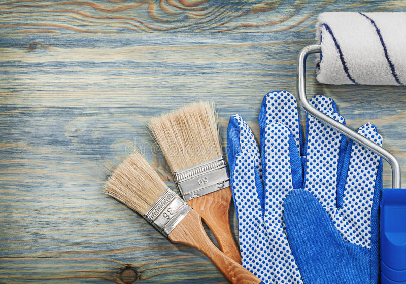 Ο κύλινδρος χρωμάτων βουρτσίζει τα λειτουργώντας γάντια στην ξύλινη κατασκευή πινάκων στοκ φωτογραφία με δικαίωμα ελεύθερης χρήσης
