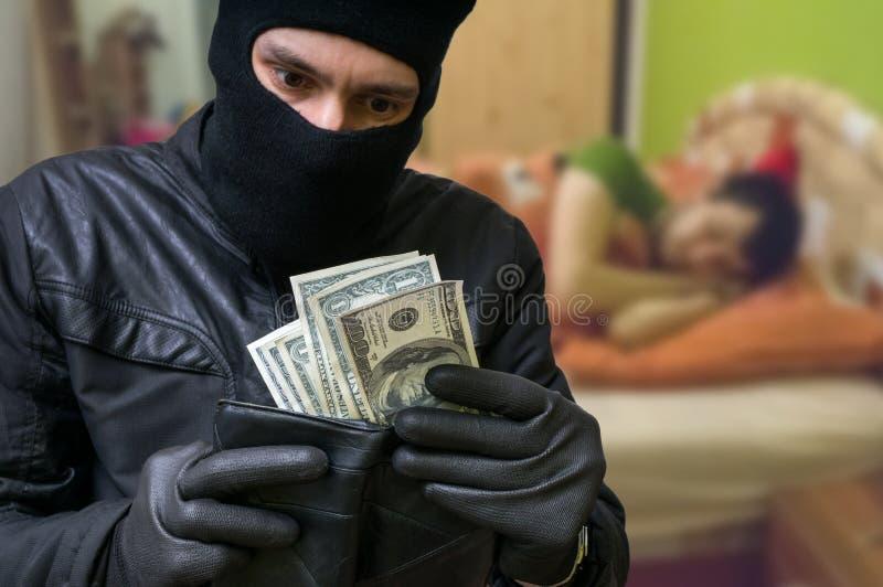 Ο κλέφτης είναι stealing χρήματα από τα χρήματα πότε είναι ύπνος ατόμων στοκ εικόνα