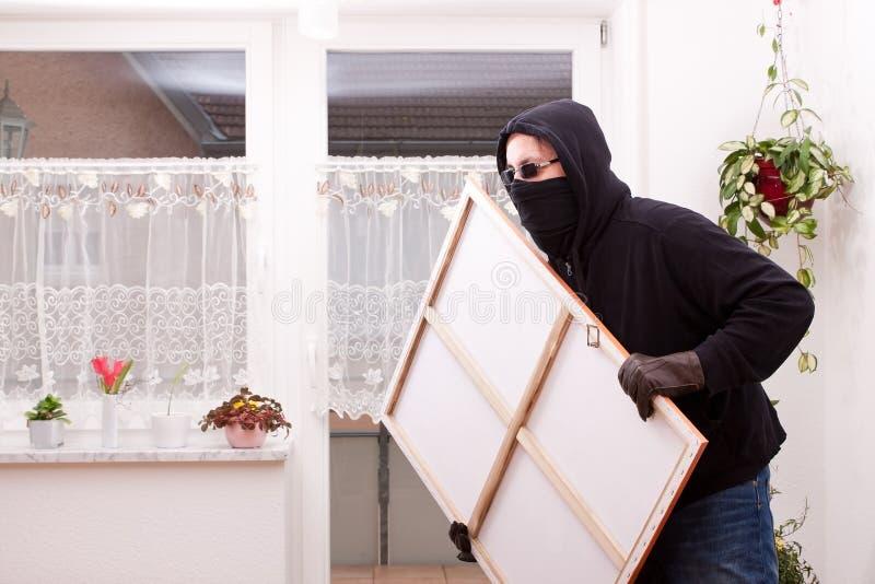 Ο κλέφτης κλέβει μια ζωγραφική στοκ εικόνες