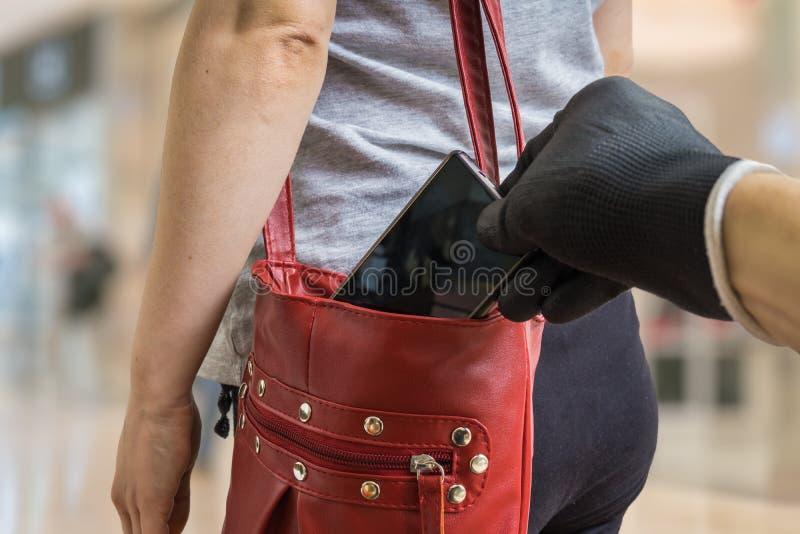 Ο κλέφτης πορτοφολάδων είναι stealing smartphone από την κόκκινη τσάντα στοκ φωτογραφίες