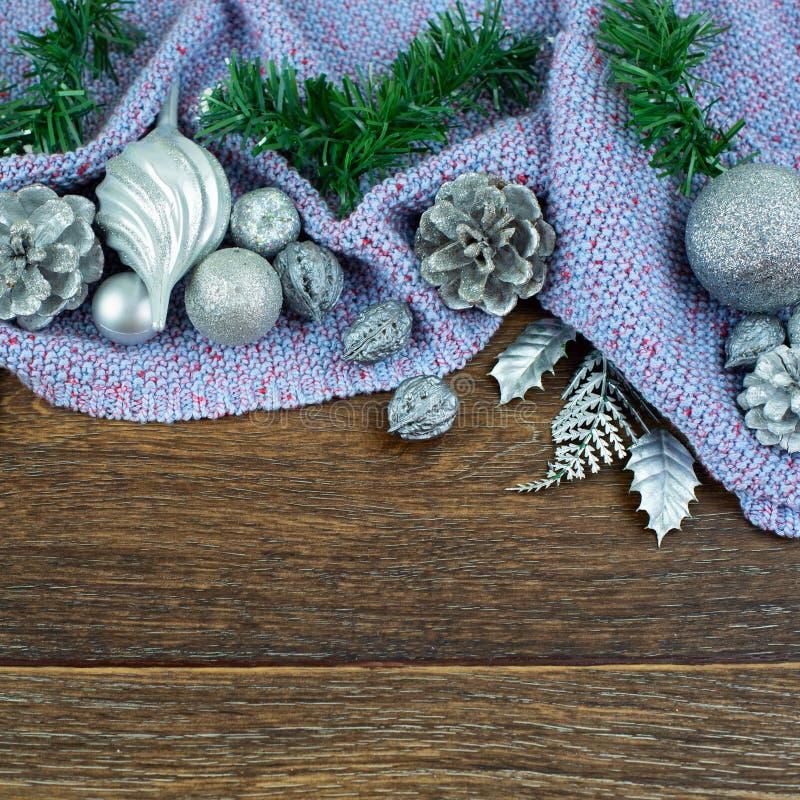 Ο λαμπρός κέδρος κλάδων κώνων καρυδιών σφαιρών σύνθεσης Χριστουγέννων αφήνει το ασήμι στο ξύλινο σκοτεινό πορφυρό καρό υποβάθρου  στοκ φωτογραφίες