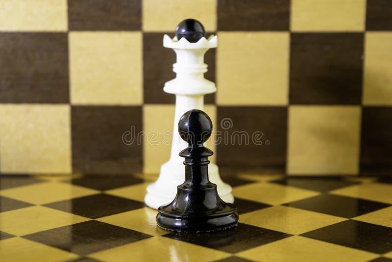 Ο λευκός βασιλιάς σκακιού και το μαύρο ενέχυρο στέκονται δίπλα σε μια σκακιέρα στοκ εικόνες με δικαίωμα ελεύθερης χρήσης